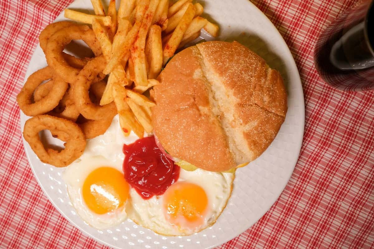 appetizing burger with french fries and eggs served on table